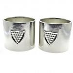 Pair of Cornish tin napkin rings with shield motif.