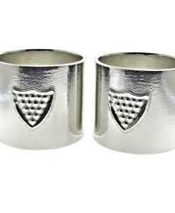 Pair of Cornish tin napkin rings with shield motif.